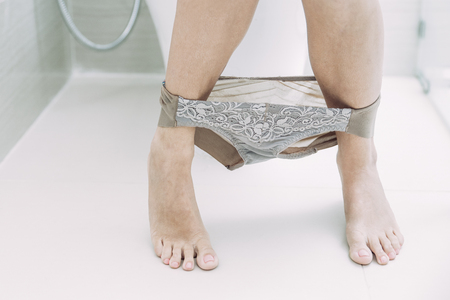 Close-up of legs and panties of young Caucasian woman sitting on toilet bowl. Female health concept