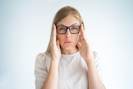 Nerdy blonde girl in eyeglasses grimacing at camera. Closeup of young Caucasian woman in glasses touching temples and staring through lens. Eyesight concept