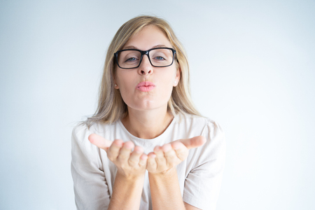 Positive young woman in glasses expressing love. Beautiful blonde Caucasian girl blowing kiss. Romance or air kiss concept
