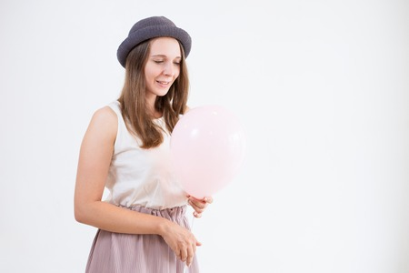Cheerful attractive girl in hat looking at balloon. Smiling pretty young woman dreaming, she standing against white wall. Wish concept
