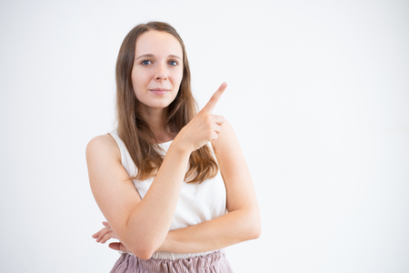 Confident young woman pointing with finger while presenting information. Serious attractive woman looking at camera and gesturing. Product manager concept Stok Fotoğraf