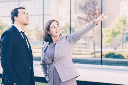 Closeup portrait of content middle-aged business man and woman relaxing and standing outdoors with office building in background. Woman is pointing at something.