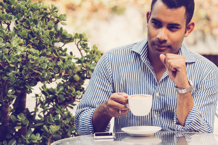 Handsome Hispanic young man with cup of coffee sitting in outdoor cafe and looking aside. Executive manager drinking coffee during lunchtime. Lunch concept Stock Photo