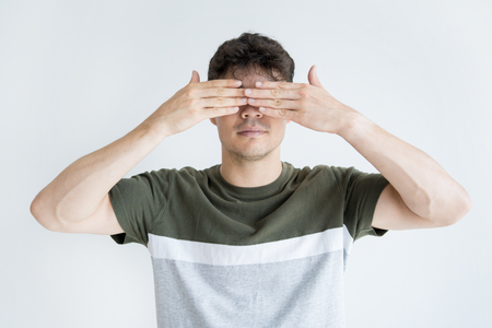 Portrait of confident young Asian man covering eyes. Vietnamese male student making face palm gesture. See no evil concept Stock Photo