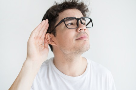 Serious young man with hearing disorder holding hand at ear. Close-up of Vietnamese guy wearing glasses listening to gossip or sound. Gossip or hearing problem concept Foto de archivo