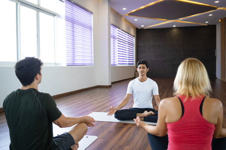 Beginners meditating with focused yoga instructor in gym. People sitting in lotus pose and keeping hands in mudra gesture. Meditation concept.