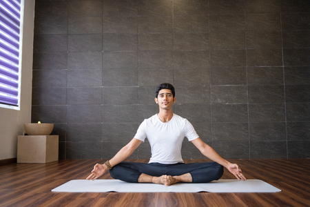 Indian yogi sitting and holding feet together in gym. Man looking at camera, keeping hands in mudra gesture and practicing yoga. Yogi concept. Front view. Banco de Imagens