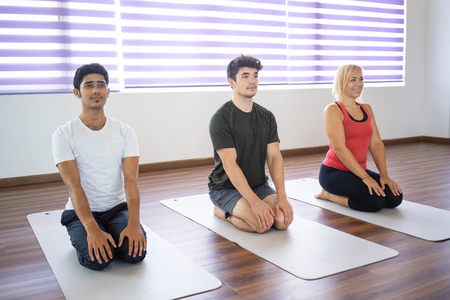 Serious beginners sitting in seiza pose on mats at yoga class. Men and woman practicing yoga in gym. Yoga class concept. Stock Photo