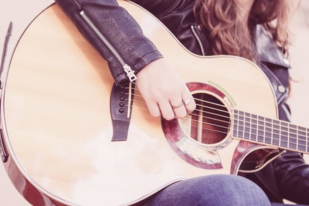 Closeup of acoustic guitar and woman hand on strings. Music and creative concept. 스톡 콘텐츠