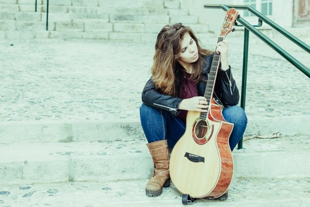 Portrait of young woman with guitar sitting on stairs and picking song. Creativity concept. 스톡 콘텐츠