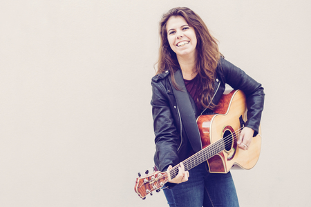 Cheerful young woman playing guitar and smiling at camera. Music and creative  concept. 스톡 콘텐츠