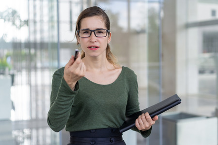 Puzzled office nerd staring at you through glasses. Pensive young woman in eyewear holding folder and pointing pen at camera, office building exterior in background. Selection concept Stok Fotoğraf