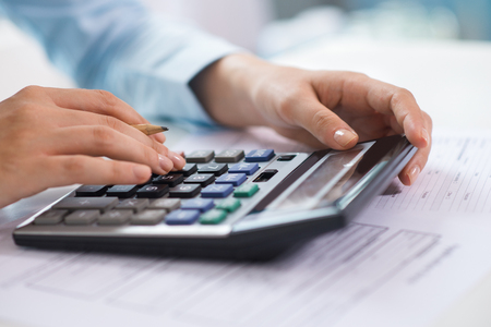 Closeup of economist working and counting data on calculator. Person pressing buttons. Finance concept. Cropped view. Foto de archivo