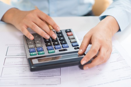 Closeup of female economist counting data on calculator. Person pressing buttons and working. Finance concept. Cropped view. Foto de archivo