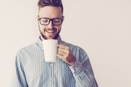 Portrait of smiling handsome young man drinking from white cup. Businessman thinking over project on his coffee break. Work balance concept
