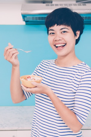 Excited young Asian woman choosing healthy eating. Cheerful healthy girl eating tomatoes with milk and looking at camera in domestic kitchen. Nutritionist concept Stock Photo