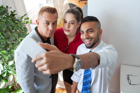 Cheerful office workers fooling and having fun during break. Two male and one female employees taking joint selfie. Work balance concept Stock Photo