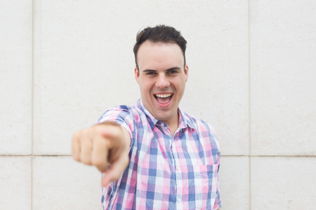 Excited successful man choosing you and gesturing to camera. Ecstatic handsome guy in casual shirt pointing with finger and looking at camera. Business coach concept