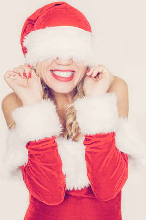 Portrait of flirty young Caucasian woman wearing Santa suit pulling hat and smiling. Christmas and New Year concept