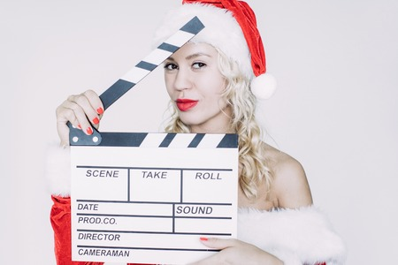 Portrait of flirty young Caucasian woman wearing Santa costume holding clapperboard and looking at camera. Christmas and Film production concept