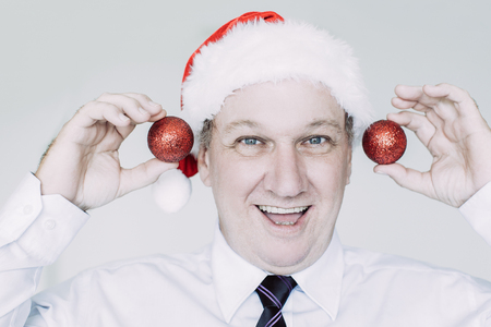 Portrait of happy senior Caucasian businessman wearing Santa hat holding baubles, looking at camera and smiling. Business Santa and office party concept