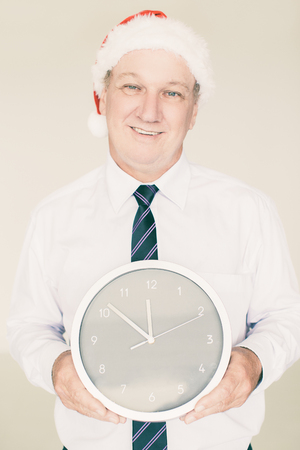 Portrait of happy senior Caucasian manager wearing Santa hat holding clock, looking at camera and smiling. Business Santa and office party concept