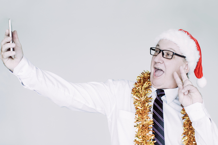 Portrait of happy senior Caucasian businessman wearing glasses, Santa hat and tinsel holding smartphone and posing for selfie showing peace gesture. Business Santa and office party concept Stock Photo