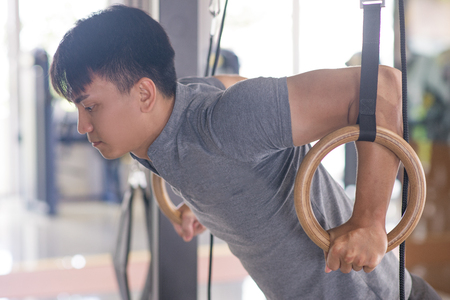 Focused Asian man training on gymnastics rings. Sporty guy in gym. Fitness and workout concept.