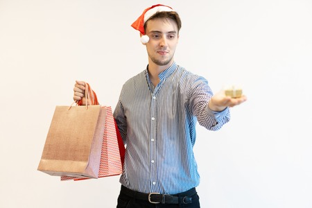 Content Christmas shopper giving little gift. Handsome young man in Santa cap holding shopping bags and showing present box on palm. Present buying concept