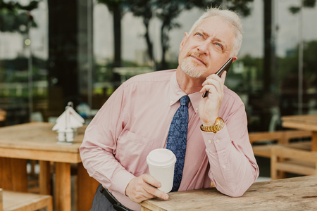 Closeup portrait of pensive senior handsome man looking upwards, holding drink in disposable cup, talking on smartphone and sitting in outdoor cafe