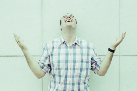 Portrait of young man wearing checked shirt standing with outstretched arms at wall and laughing. Happiness and emotion concept