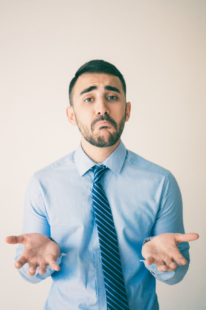 Portrait of upset young man shrugging with sad face. Confused office clerk demonstrating helpless gesture. Do not know what to do  and fail concept Stock Photo