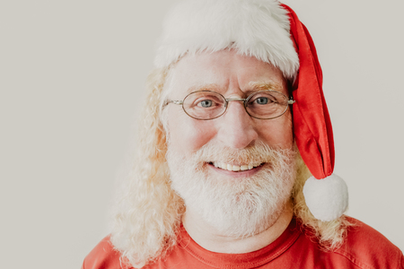 Closeup portrait of smiling senior man wearing glasses, Christmas hat and looking at camera. Christmas concept Stock Photo