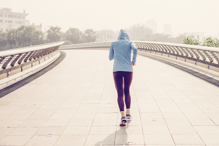 Young attractive woman wearing sportswear, training and jogging on bridge with city in background. Back view. Banco de Imagens