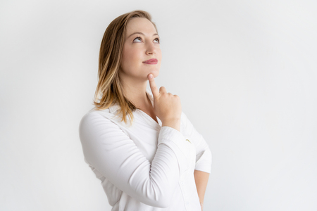 Dreamy beautiful woman touching chin with finger. Young lady looking upwards. Anticipation concept. Isolated view on white background. Stock Photo