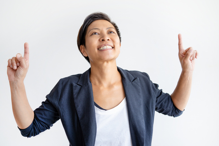 Smiling Asian woman pointing and looking upwards. Positive young lady. Promotion concept. Isolated front view on white background.