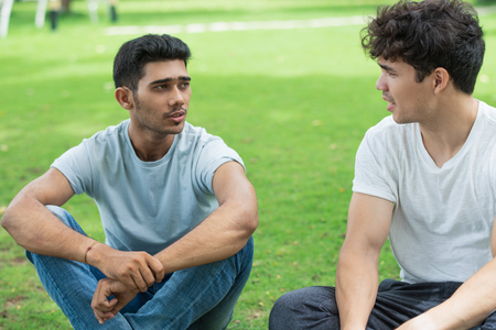 Serious Indian guy sharing problem with friend in summer park. Handsome young men sitting on grass and talking. Chatting concept Stock fotó