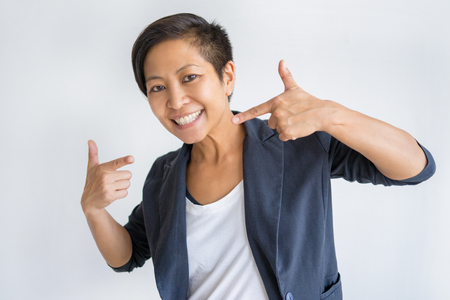 Smiling Asian woman pointing at herself and looking at camera. Confident lady. Self-reliance concept. Isolated front view on white background. Stockfoto