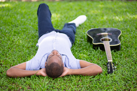 Black man lying upside down on grass and guitar. Handsome young man in park. Guitarist and rest concept.