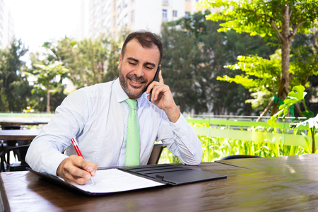Happy businessman talking on phone and working with document at cafe. Portrait of mature Caucasian executive working outdoors. Freelance pr communication concept