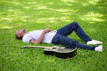 Relaxed black man lying on grass with guitar in park. Handsome young man having rest. Guitarist and rest concept.