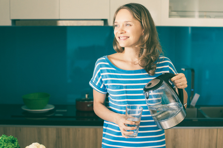 Closeup portrait of smiling young beautiful woman pouring water from kettle into glass and standing in kitchen. Drinking water concept. Front view. Stok Fotoğraf