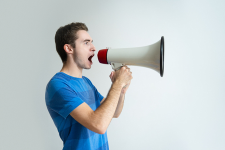 Serious man holding megaphone and screaming into it. Young guy looking away. Advertisement concept. Isolated side view on white background.