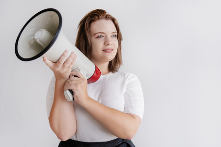 Pensive young female activist holding loudspeaker. Smiling woman with megaphone leading process of work. Leadership concept Stock Photo