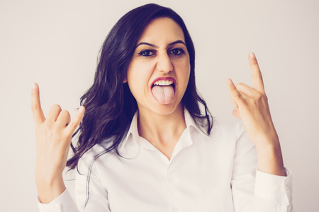 Closeup portrait of cool middle-aged beautiful dark-haired woman looking at camera, showing tongue and rock gesture. Cool, successful business person concept. Isolated front view on white background. 스톡 콘텐츠