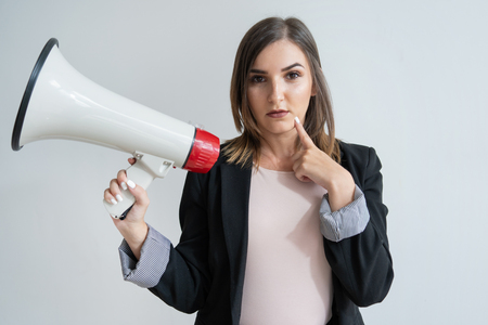 Pensive young Caucasian woman holding megaphone and touching chin. Pretty dark-haired manager in smart suit looking at camera in thought. New advertising idea concept Banco de Imagens
