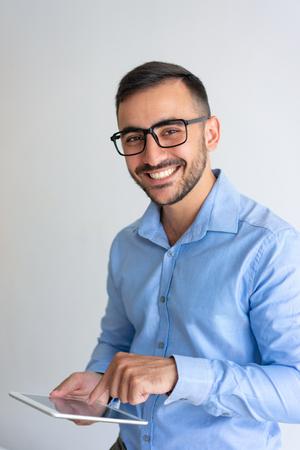 Un homme d'affaires joyeux teste une application PC mobile. Jeune homme à lunettes et chemise décontractée à l'aide d'une tablette et souriant à la caméra. Concept de technologie de l'information Banque d'images