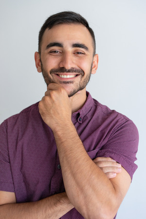 Closeup of happy successful handsome guy with stubble in casual. Young man touching chin and smiling at camera. Male portrait concept