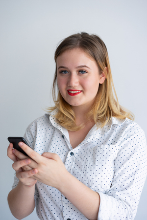 Content phone user testing new mobile app. Positive young woman using smartphone and looking at camera. SMS or chatting concept