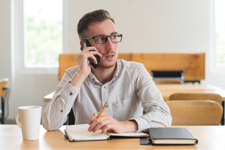 Male student talking on phone and doing homework at desk in classroom. Young man using smartphone. Education and technology concept. Front view.